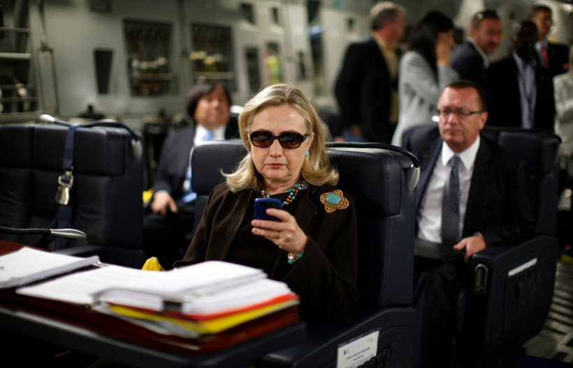 U.S. Secretary of State Hillary Clinton checks her PDA upon her departure in a military C-17 plane from Malta bound for Tripoli,  Libya October 18, 2011.  REUTERS/Kevin Lamarque  (LIBYA - Tags: POLITICS)         FOR BEST QUALITY IMAGE ALSO SEE: GF2EA1P10ZY01 - RTR2ST4W
